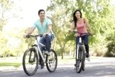 6128064-young-couple-riding-bike-in-park