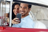 9749840-happy-young-man-and-woman-smiling-while-taking-snapshot-with-cell-phone-camera-from-red-vintage-conv